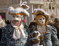 Masked persons in costume on San Marco Square in Venice, Italy. Royalty Free Stock Image