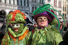 Masked persons in costume on San Marco Square in Venice, Italy. Stock Photos