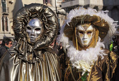 Masked persons in golden costume on San Marco Square in Venice, Royalty Free Stock Photography