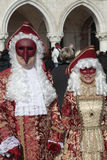 Masked persons in magnificent red and gold costume on San Marco Stock Images