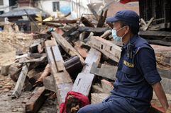 Masked Policeman Guarding the Devastated Site. A policeman guarding the devastated site at Basantapur Durbar Square.The 7.8-magnitude earthquake that devastated royalty free stock photos
