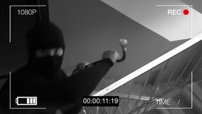 The masked robber breaks removing the surveillance camera mount.  Stock Photo