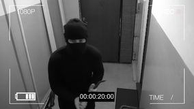 The masked robber burst through the door and broke the security camera with a tire iron.  Stock Photos