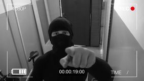 The masked robber burst through the door and threatened with a knife in CCTV camera.  Stock Photography