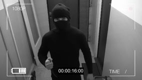 The masked robber burst through the door and threatened with a knife in CCTV camera.  Royalty Free Stock Images