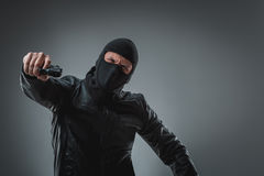 Masked robber with gun, looking into the camera. Stock Photography