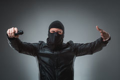 Masked robber with gun, looking into the camera. Stock Image