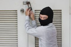 Masked robber using a lock picking tool to breaking and entering into a house. Criminal crime concept. Royalty Free Stock Images