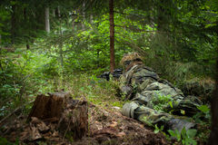 Masked soldier. Uderlies the trees Royalty Free Stock Image