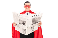 Masked superhero reading the news Royalty Free Stock Photography