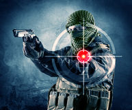 Masked terrorist man with gun and laser target on his body. Concept stock image