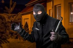 Masked thief in balaclava with crowbar wants to rob a house royalty free stock photos