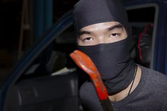 Masked thief with balaclava holding crowbar to breaking into a car. Crime concept.  Stock Photos