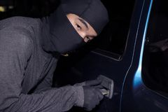Masked thief with balaclava with key to breaking into a car. Crime concept.  Stock Photo