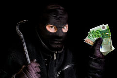 Masked thief in balaclava with stolen money isolated on black. Background Royalty Free Stock Photos