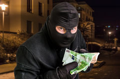 Masked thief in balaclava with stolen money Stock Photography