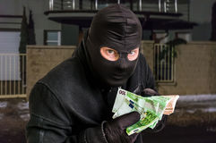 Masked thief in balaclava with stolen money Stock Image