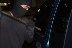 Masked thief with balaclava using crowbar to breaking into a car. Crime concept royalty free stock photography