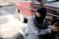 Masked thief in black balaclava trying to break into car. Criminal crime concept. Masked thief in black balaclava trying to break into car. Criminal crime royalty free stock photography