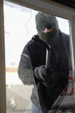 Masked Thief Breaking Glass. With crowbar to get into house through window Stock Photography