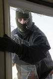 Masked Thief Breaking In Through Window Stock Photo