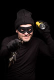 Masked thief. Burglar in black balaclava with flashlight and keys at night. Handsome man going to do robbery or burglary of house. Isolated on black Royalty Free Stock Image