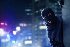 Masked thief hiding on the wall. At night Royalty Free Stock Photo