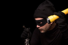 Masked thief. Thief with robbery mask holding flashlight behind over black background. Man in black clothes holding keys from expensive house. Isolated on black Royalty Free Stock Photo