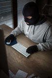 Masked thief sitting in front of computer Stock Photos