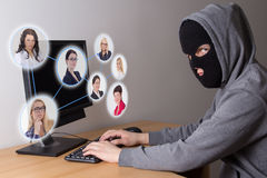 Masked thief stealing data from computers. Masked hacker stealing data from computers Royalty Free Stock Photography