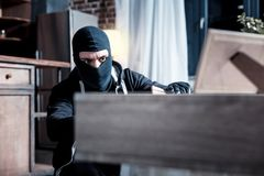 Masked thief stealing important papers. Thief. Serious dark-eyed masked thief wearing a black uniform and holding a folder while stealing important papers from Stock Images