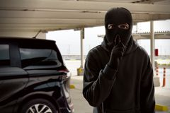 Masked thief trying to steal car stock images