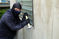 Masked thief using a hammer trying to break windows. And the Shocked face expression stock photos