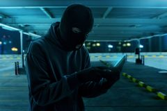 Masked thief using mobile phone stock images