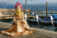 Masked woman with pink headdress. In Venice at sunset Royalty Free Stock Photo