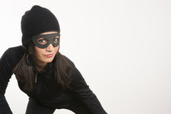 Masked Woman Sneaking Lurking Around Looking For Something to Steal. Beautiful woman dressed in black and up to no good Royalty Free Stock Photography