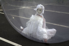 Masked woman in a sphere. AURILLAC, FRANCE- AUGUST 18: Aurillac International Street Theater Festival, Cie Jimyprod, a masked woman is dancing in a transparent royalty free stock image
