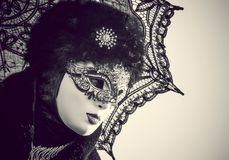Masked woman in Venice carnival. Portrait of a carnival black masked woman with an umbrella in a monochromatic image Royalty Free Stock Photos