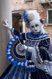 Masked woman wearing a decorative blue dress standing on next to an old stone column during Venice Carnival stock photos