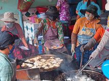 Masked Women. These women are cooking the popular delicacy in Ho Chi Minh City known as 'Banh Khot, fried prawn in batter. Ideal for promotional write up for Stock Photos