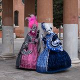 Masked women in bright colored ornate costumes at Venice Carnival. Two women in masks and ornate blue and pink costumes standing in front of pillars at a Stock Photo