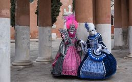 Masked women in brightly colored pink and blue costumes at Venice Carnival. Two women in masks and ornate blue and pink costumes standing in front of pillars at Royalty Free Stock Photography