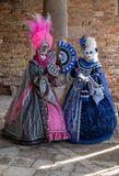 Masked women in ornate blue and pink costumes standing next to a pillar during the Venice Carnival. Italy Carnival di Venezia Stock Photos