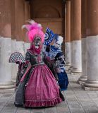 Masked women in ornate costumes at Venice Carnival. Two women in masks and ornate blue and pink costumes standing in front of pillars at a monastery during Royalty Free Stock Photos