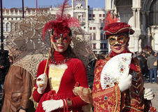 Masked women in red costume on San Marco Square, Venice Royalty Free Stock Image