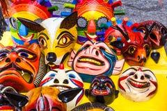 Masken schnitzten in hölzernem und in handgemaltem mit hellen Farben stockbild