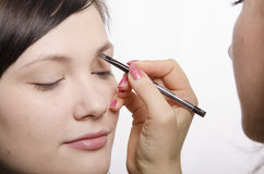 Maskenbildner bei Make-up holt Augenbrauenstiftmodell Lizenzfreie Stockfotografie