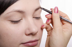 Maskenbildner bei Make-up holt Augenbrauenstiftmodell Lizenzfreies Stockbild