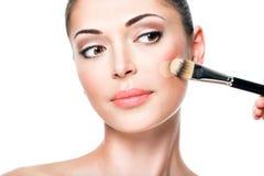 Maskenbildner, der flüssige Ton- Grundlage auf dem Gesicht anwendet Lizenzfreie Stockbilder
