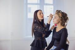 Maskenbildner, der flüssige Ton- Grundlage auf dem Gesicht der Frau anwendet Stockbild